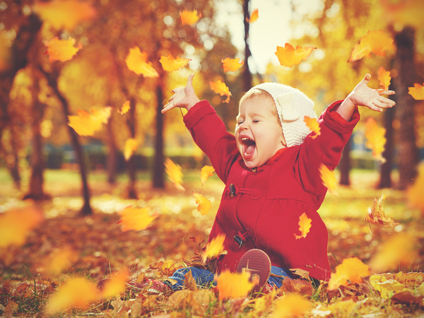 happy little child baby girl laughing and playing in the autumn on the nature walk outdoors